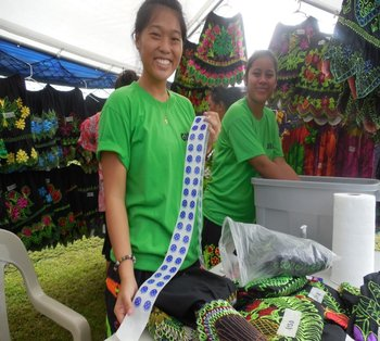 A trade show participant shows off a roll of the 'Buy FSM Made' stickers in Pohnpei.