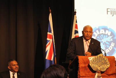 Fiji Prime Minister Voreqe Bainimarama addresses the Fiji Trade and Investment Symposium in Auckland as Minister for Trade, Industries and Tourism Faiyaz Siddiq Koya looks on.