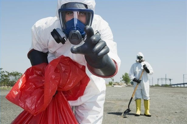 man in hazard suit and red trash bag looking at camera
